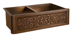 Double bowl copper farmer sink with stylized flower motif