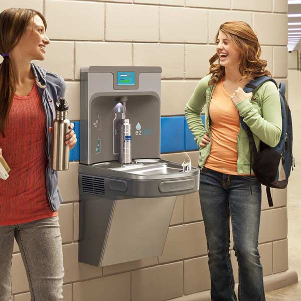 Girls laughing around school water filter drinking fountain